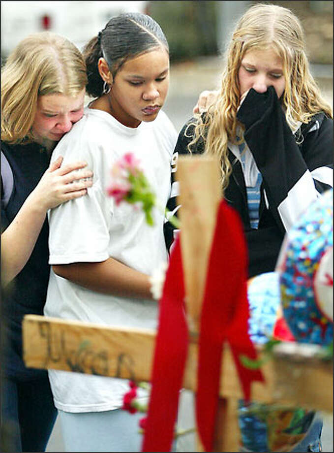 Marcus Morgan's friends and schoolmates Erika Carlson, Christina Figueroa and Katie Closson, left to right, mourn at a memorial in his honor in Lakewood. Morgan was killed by a bus while walking to Mann Middle School Monday. Photo: Dan DeLong, Seattle Post-Intelligencer / Seattle Post-Intelligencer