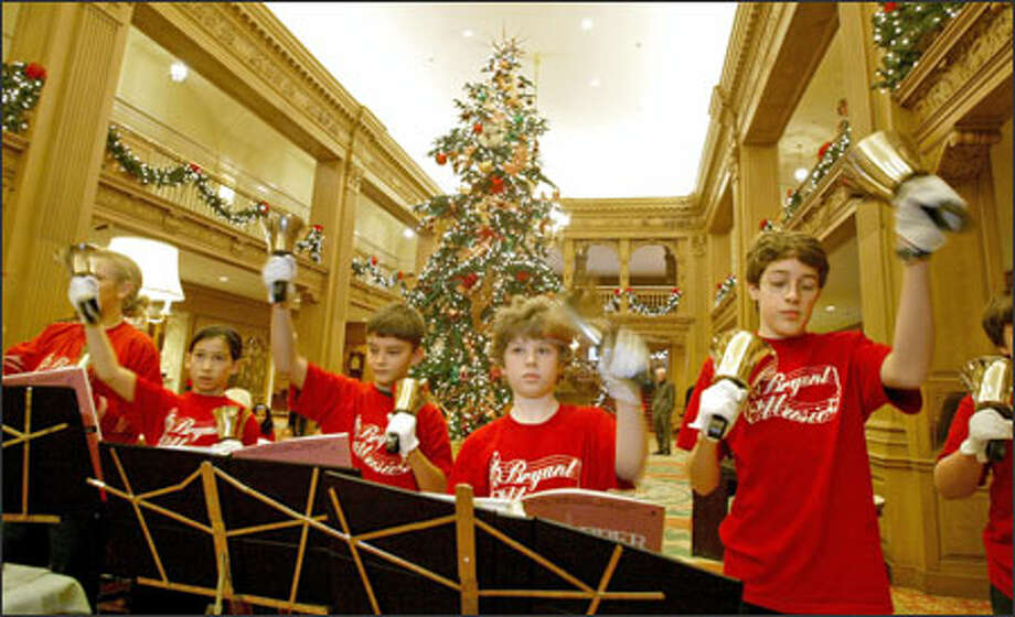 Members of the Bryant Elementary School bel choir, from left, Naomi Anderson, Rachel Abramson, Brian Murray, Brendan McMullen and Jordan Macias, perform at The Fairmont Olympic Hotel in downtown Seattle this week. A 25-foot Christmas tree in the hotel lobby is in the background. Photo: Scott Eklund, Seattle Post-Intelligencer / Seattle Post-Intelligencer