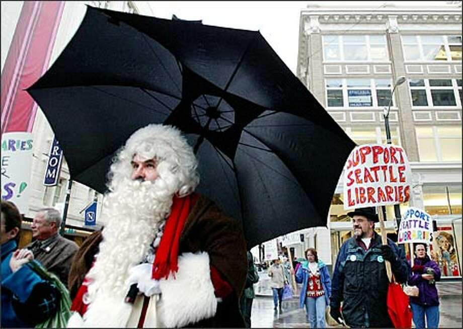 The city has been naughty, librarians say, by forcing a weeklong closure of the library system to save money. Santa Claus, played by John Sheets, was among the Seattle Public Library staffers who protested at Westlake Center. Photo: Paul Joseph Brown, Seattle Post-Intelligencer / Seattle Post-Intelligencer
