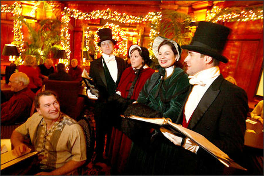 Bobby Lowe, above left, of Bellevue enjoys the entertainment of the Dickens Carolers at the Sorrento Hotel in Seattle. This group of singers consists of, from left, Tom Cooper, Ali Mattack, Ann Snow and CAm Matack (brother of Ali). Photo: Scott Eklund, Seattle Post-Intelligencer / Seattle Post-Intelligencer