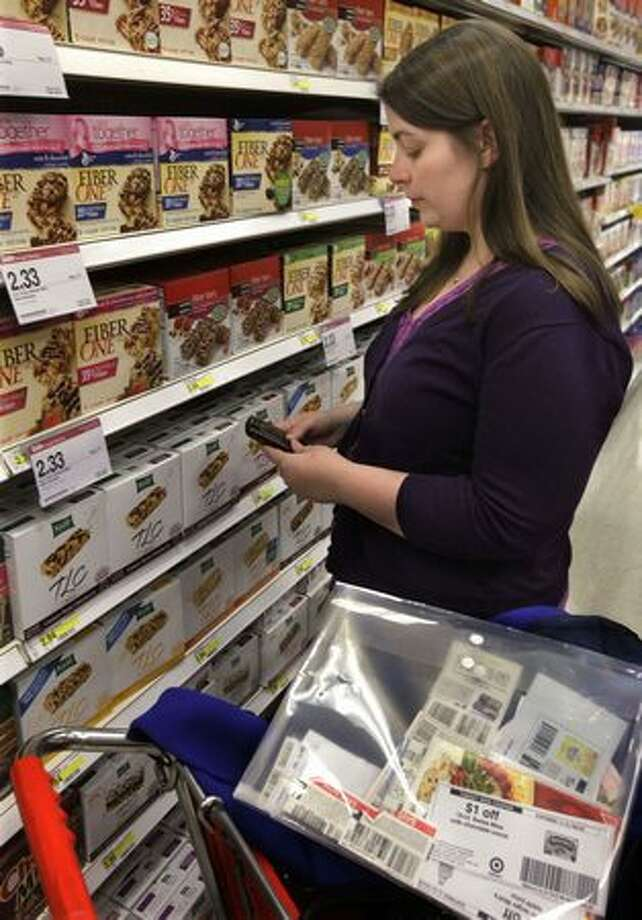 In this photo made Dec. 8, Kelly Norby uses her Blackberry to compare prices and find coupons before making a purchase at a Target store in Wheeling, Ill. (AP Photo/(M. Spencer Green) Photo: Associated Press / Associated Press