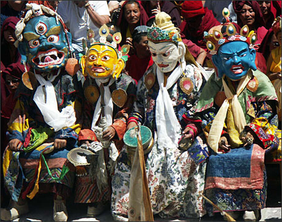 Masked monks at the Hemis Festival depict four of the eight forms of Buddha. (JANE POYNTER PHOTOS)
