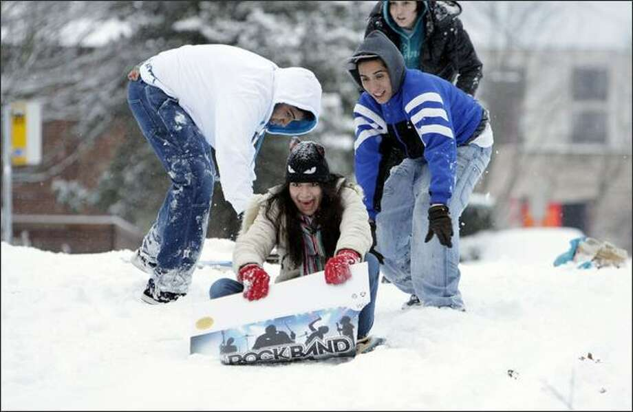 Diana Sandoval, 20, gets a push from Louis Calderon and Daniel Sandoval, right, on Thursday morning. Sandoval just arrived from Mexico City for a Seattle visit last night. The street they were sledding on was closed to car traffic. Photo: Meryl Schenker, Seattle Post-Intelligencer / Seattle Post-Intelligencer