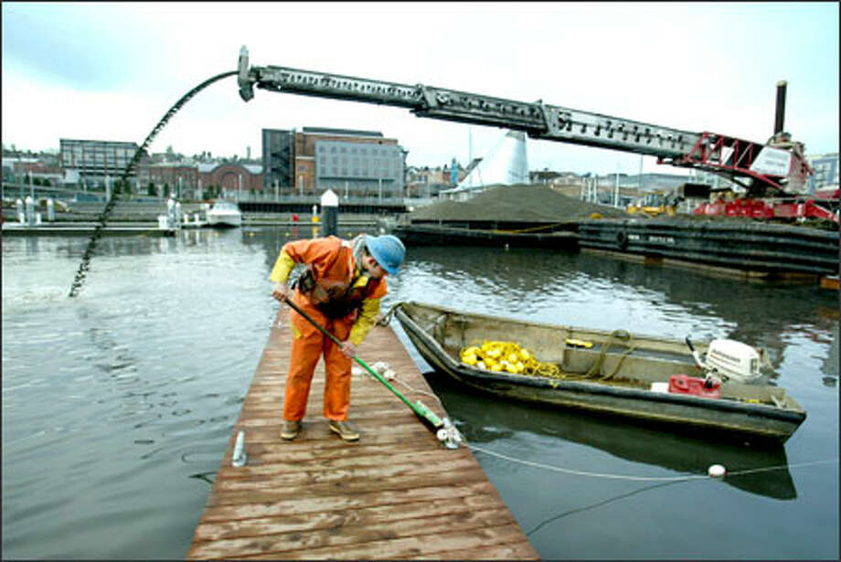 Cody Woodruff of Manson Construction sweeps sediment off a dock on the Foss Waterway in Tacoma. As part of the cleanup, Manson Construction was hired to deposit a gravel mixture to cover up some of the contaminated areas. Photo: Scott Eklund, Seattle Post-Intelligencer / Seattle Post-Intelligencer