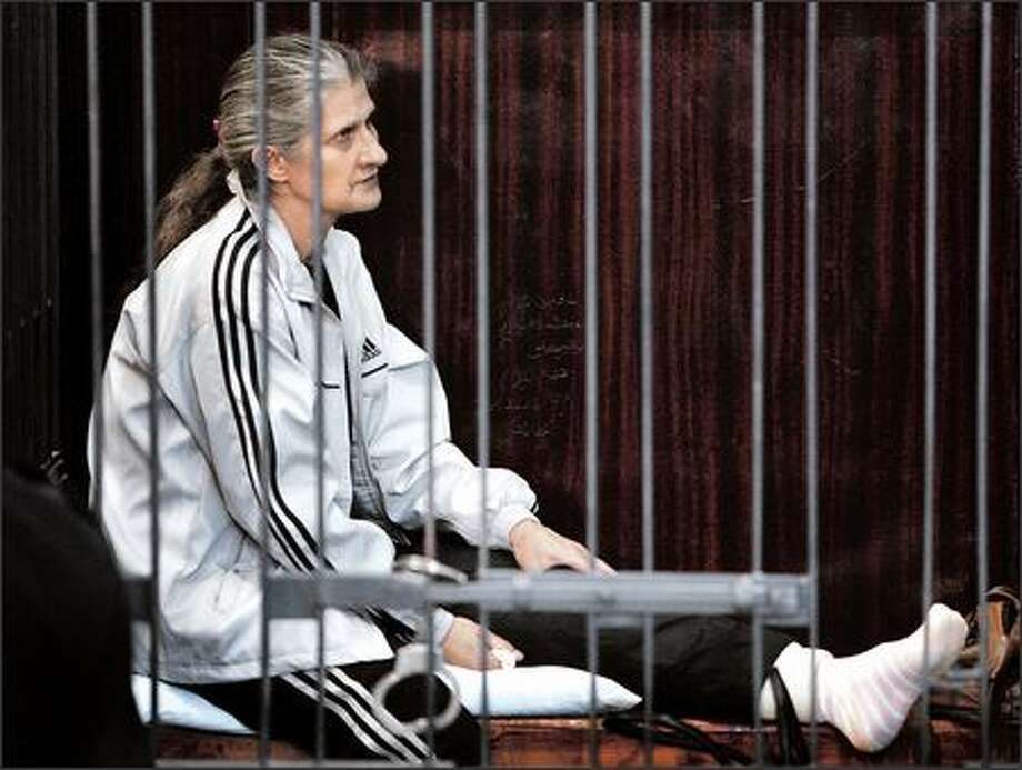 Bulgarian nurse Snezhana Dimitrova, who appeared to have a problem with her left leg, sits in the caged dock at the trial of five Bulgarian nurses and a Palestinian doctor in Tripoli, Libya. Photo: Associated Press / Associated Press