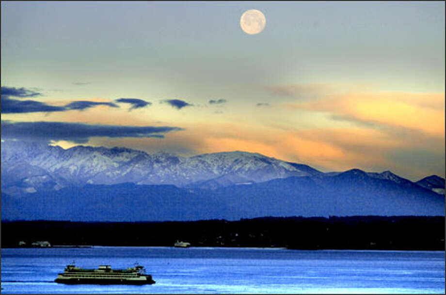 One day before the arrival of winter, December's full moon, also called a Cold Moon, appears in the morning sky above Puget Sound and the Olympic Mountain range yesterday. Photo: Renee C. Byer, Seattle Post-Intelligencer / Seattle Post-Intelligencer
