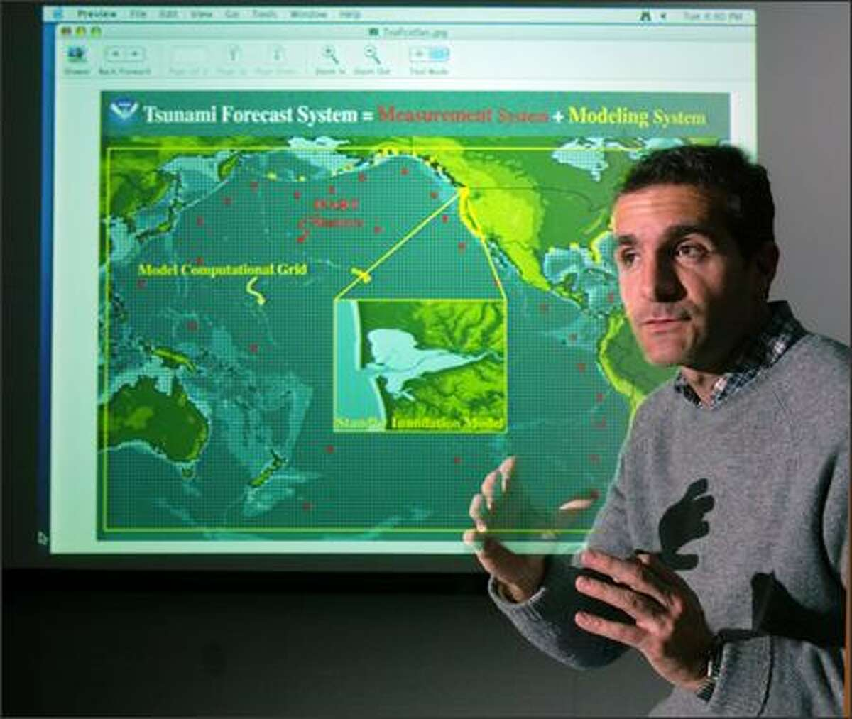 The Trump administration wants to slash all money for the ShakeAlert earthquake warning system on the West Coast. Here, NOAA research scientist Diego Arcas talks about NOAA's Tsunami Forcast, Measurement and Modeling Systems. Behind him is a projected map of the Pacific Rim showing DARTs (Deep Ocean Assesment of Tsunamis; Red dots) and SIMs (Standby Inundation Mode; yellow squares) that will make up the building blocks of the Tsunami Warning System. The insert shows the Ocean Shores-Grays Harbor area of the Washington coast.