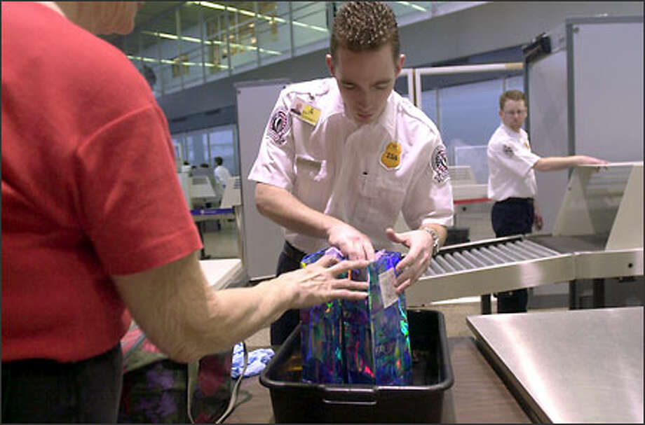 Airport security screener Scott Meyer goes through Gloria Nelson's things at Sea-Tac Airport yesterday. Nelson had a hair clip that showed up on the X-ray machine. Photo: Ron Wurzer, Seattle Post-Intelligencer / Seattle Post-Intelligencer