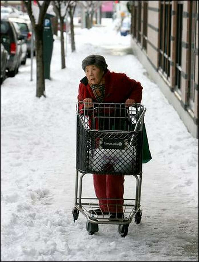 Kimi Akashi, 86, pushes her cart and looks for a taxi after shopping Monday at Uwajimaya in the International District. Photo: Scott Eklund, Seattle Post-Intelligencer / Seattle Post-Intelligencer