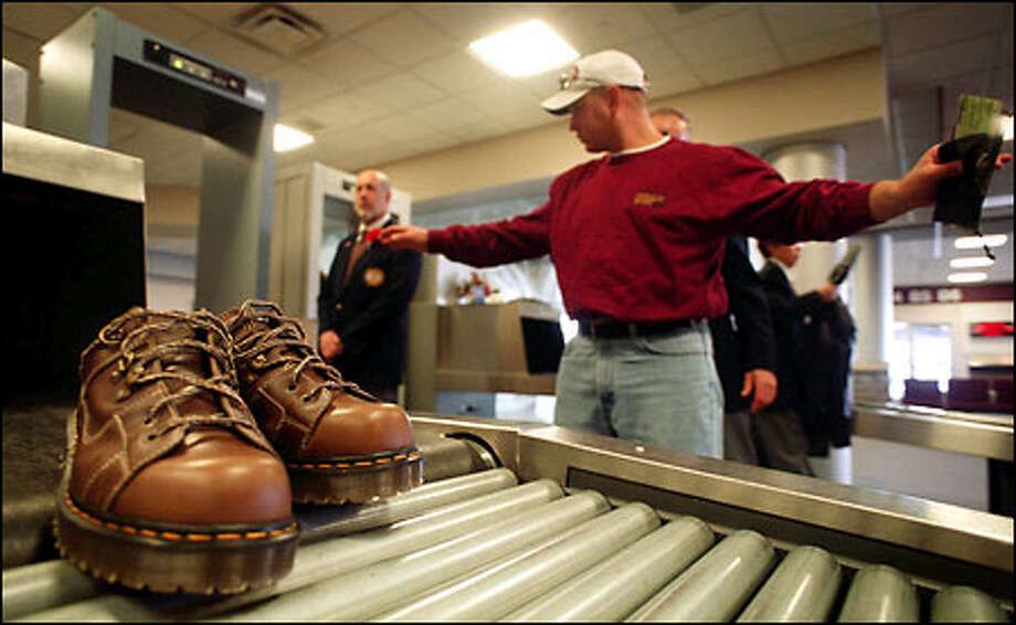 "As his shoes roll out of the airport security X-ray machine, Dave Peterson is searched by airport security at the Cedar Rapids, Iowa, Airport. Peterson wasn't bothered. ""The safer the better -- I don't mind at all,"" he said. Photo: Associated Press / Associated Press"