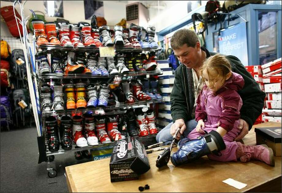 Greg Kenneth and his daughter Taylor, 4, look over new ski bindings, part of a Christmas gift for Greg's wife, on Tuesday at Second Ascent. The Ballard shop sells used and new ski equipment. Photo: Joshua Trujillo, Seattlepi.com / seattlepi.com