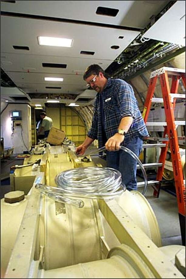 Craig Boyden works on water ballast tanks for the 777-300ER that will used for flight testing. Boeing's commercial plants in Renton and Everett will make airplanes with far fewer workers than in the past. Photo: Phil H. Webber, Seattle Post-Intelligencer / Seattle Post-Intelligencer