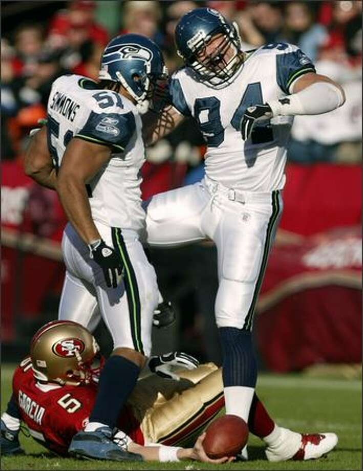 Seattle Seahawks linebacker Chad Brown, right, celebrates with teammate Anthony Simmons after Brown sacked San Francisco 49ers quarterback Jeff Garcia, bottom, in the first quarter in San Francisco. Photo: Associated Press / Associated Press