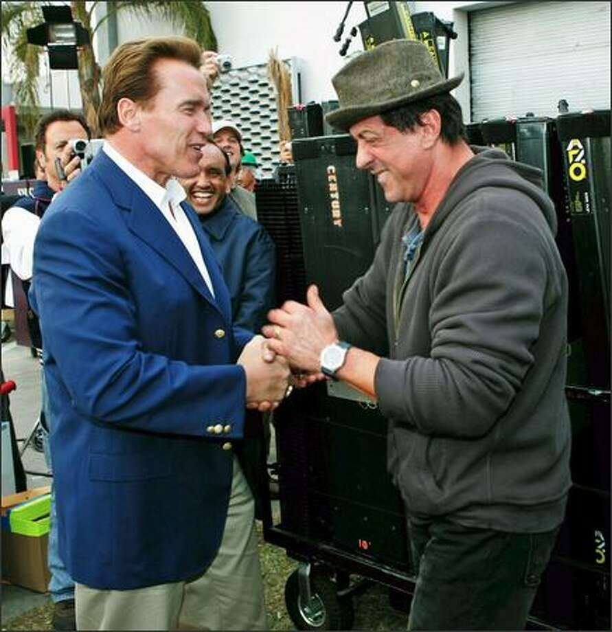 "Two movie bruisers meet on the set of the upcoming flick, ""Rocky Balboa,"" last week and L.A. Mangled English likely was the result as California Gov. Arnold Schwarzenegger presses ham hocks with Sly Stallone, who is starring in yet another ""Rocky"" reprise. Photo: Associated Press / Associated Press"