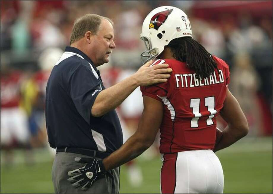 Head coach Mike Holmgren of the Seattle Seahawks greets wide receiver Larry Fitzgerald #11 of the Arizona Cardinals on Sunday at University of Phoenix Stadium in Glendale, Arizona. Photo: Getty Images / Getty Images
