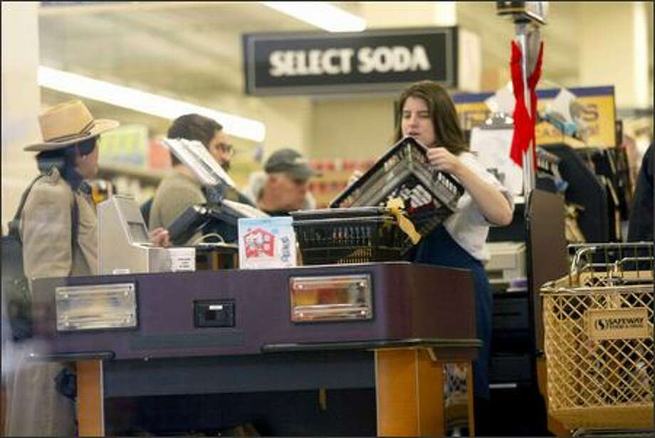 Contracts for Safeway employees, such as this checker in Seattle, will be negotiated in 2004. Workers in California stores have been on strike for two months. Photo: Phil H. Webber, Seattle Post-Intelligencer / Seattle Post-Intelligencer