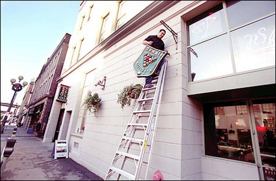 Rolando Salinas, general manager of Temple Billiards, removes the sign so he can put up a new one. The business is adding a lounge downstairs. Photo: Meryl Schenker, Seattle Post-Intelligencer / Seattle Post-Intelligencer