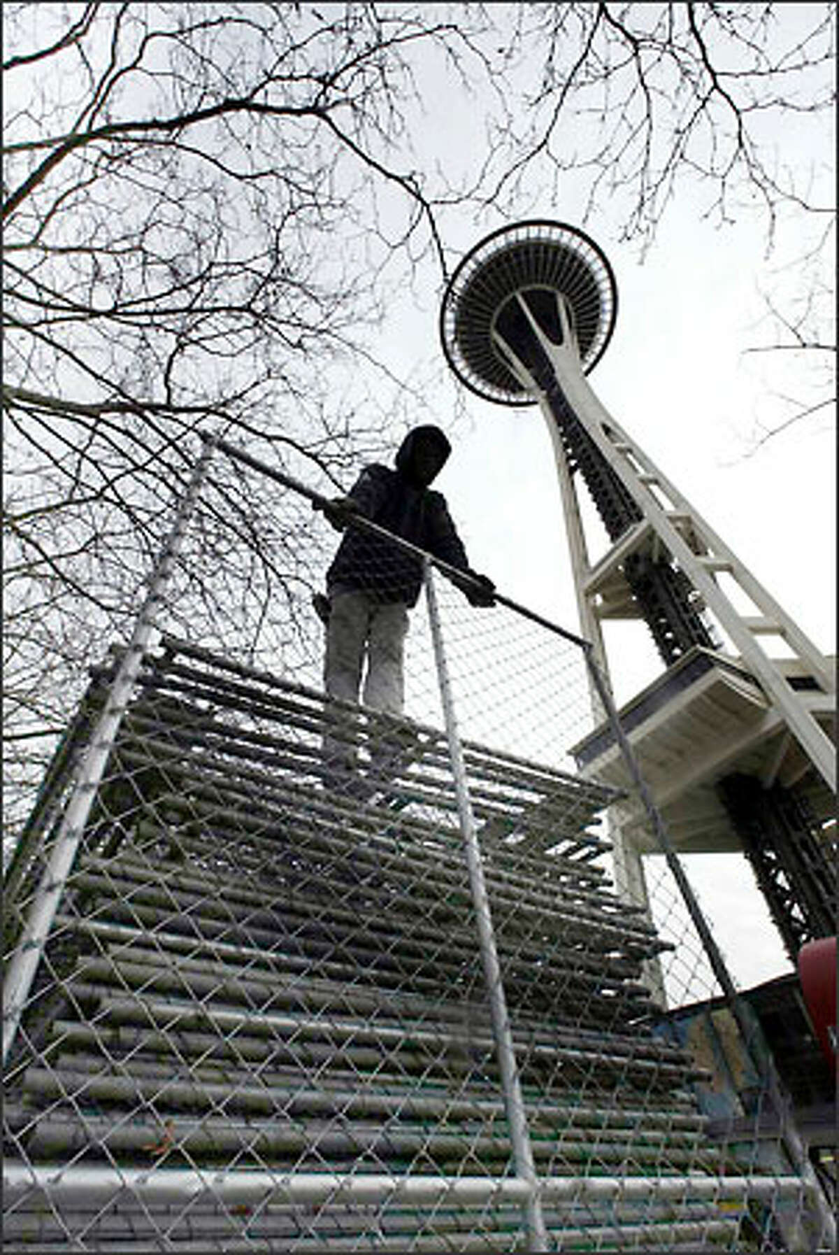 Victaly Soloneko from National Rent-a-Fence unloads sections of chain link that will form a security fence line around the Space Needle for New Year's Eve.