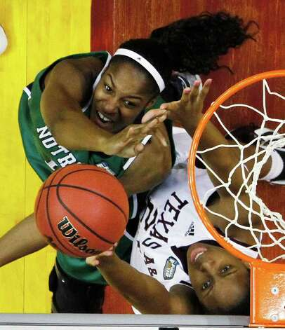 Notre Dame's Devereaux Peters, left, puts up a shot under pressure from Texas A&M's Adaora Elonu in the second half of the women's NCAA Final Four college basketball championship game in Indianapolis, Tuesday, April 5, 2011. Photo: AP