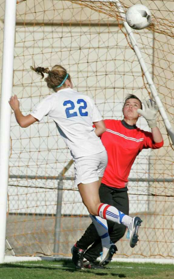 SPORTS; SOC 5A 3RD ROUND GIRLS JMS; 04/05/11;Steele goalkeeper Jennifer Sanchez makes an early save against MacArthur forward Kelsey Falcone (22) as the two teams met in a Class 5A third round girls soccer match, Tuesday, April 5, 2011 at Blossom Soccer Stadium West in San Antonio. ( Photo by J. Michael Short / SPECIAL ) Photo: J. Michael Short, SPECIAL TO THE EXPRESS-NEWS / THE SAN ANTONIO EXPRESS-NEWS