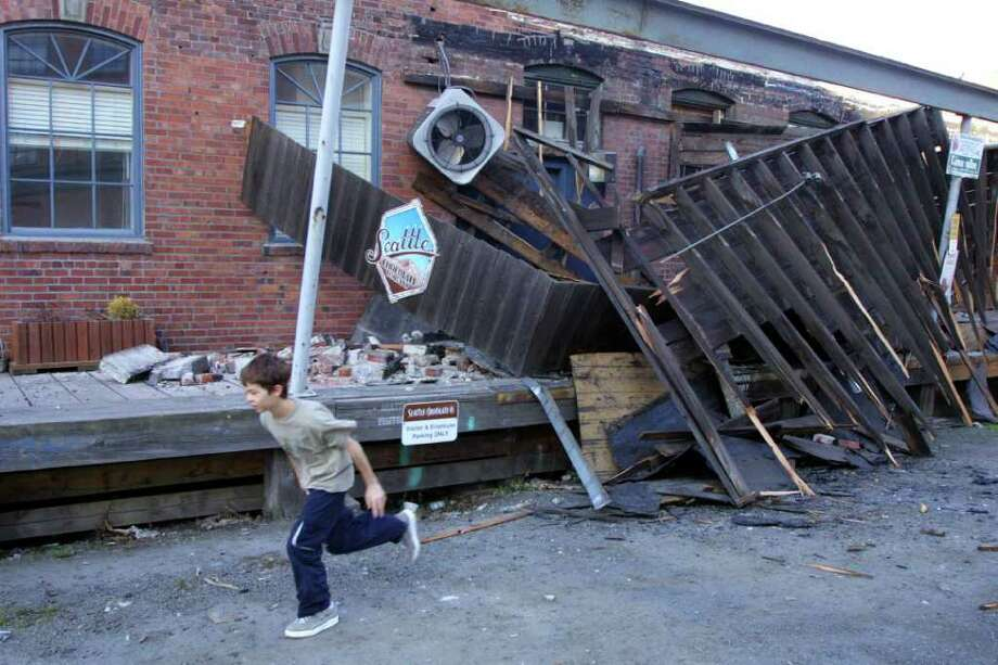 A boy runs past damage to the Chocolate Candy Manufacturing Co. on the south side of downtown on Feb. 28, 2001, after the 6.8-magnitude Nisqually Earthquake. Photo: DAN LEVINE, Getty Images / AFP