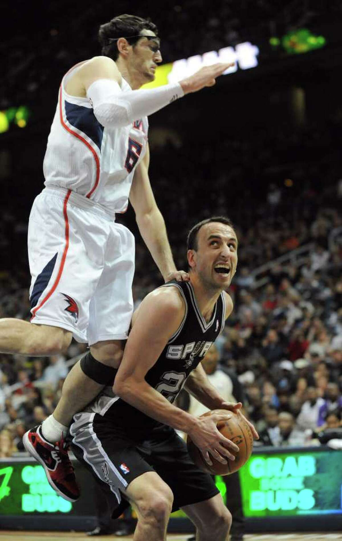 Atlanta Hawks guard Kirk Hinrich, left, commits a flagrant foul on San Antonio Spurs guard Manu Ginobili, of Argentina, in the second half during an NBA basketball game Tuesday, April 5, 2011, in Atlanta. The Spurs defeated the Hawks 97-90.