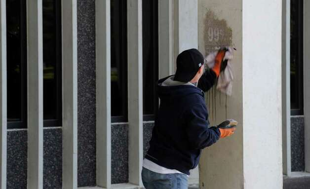 University at Albany worker Josh Bloomfield cleans a spray-painted column.   (Skip Dickstein / Times Union) Photo: SKIP DICKSTEIN / 2008