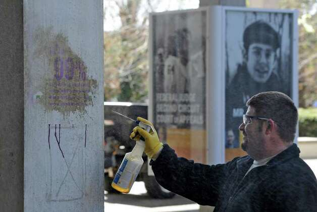 University at Albany worker Art Henderson cleans a column vandalized near the campus' Academic Podium.   (Skip Dickstein / Times Union) Photo: SKIP DICKSTEIN / 2008