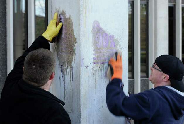 UAlbany facilities workers Art Henderson, left and Josh Bloomfield clean a pillar marred with graffit.  (Skip Dickstein / Times Union) Photo: SKIP DICKSTEIN / 2008