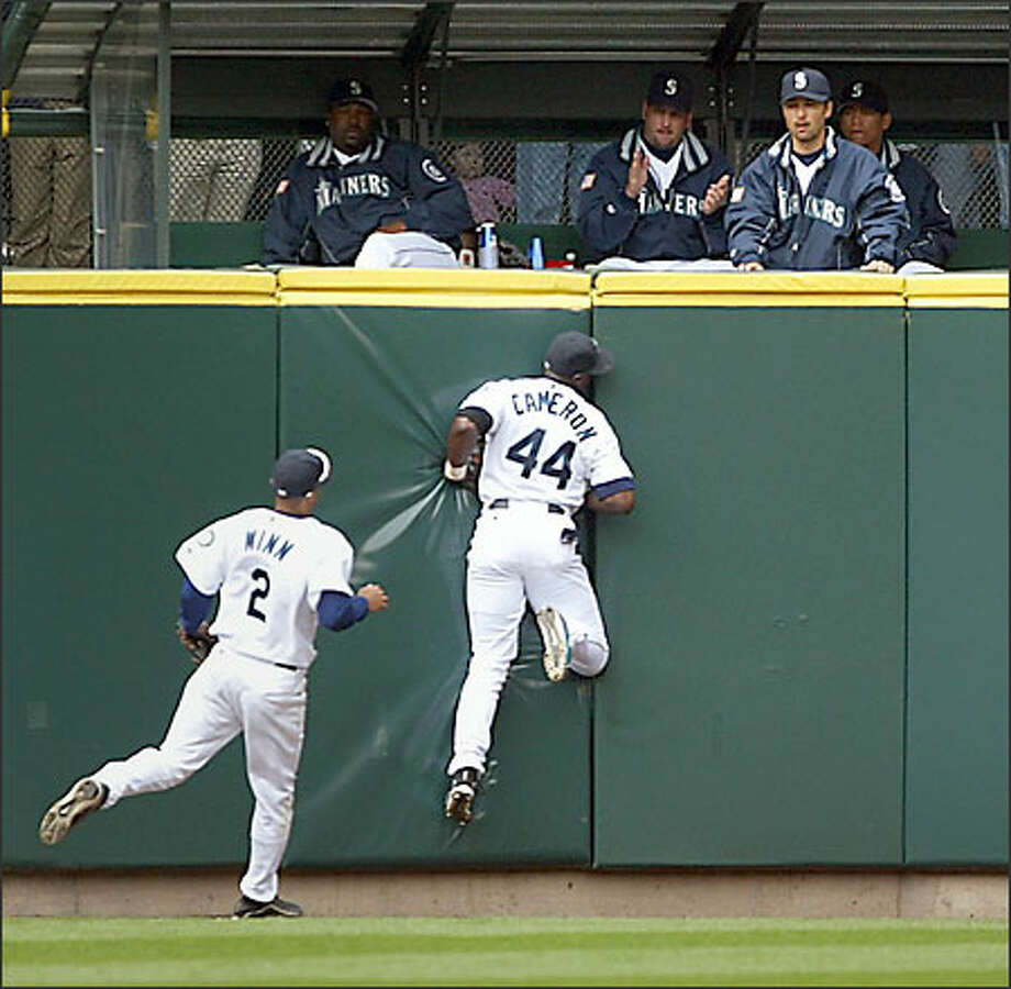 Mike Cameron hits the wall after making a nice catch of a fly ball off the bat of Anaheim's Benji Molina. Photo: Dan DeLong, Seattle Post-Intelligencer