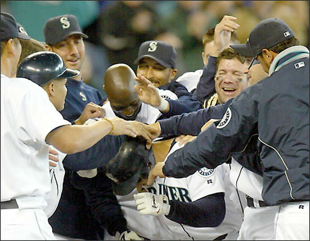 Bret Boone receives a hero's welcome after beating Texas with a solo home run in the 13th inning.