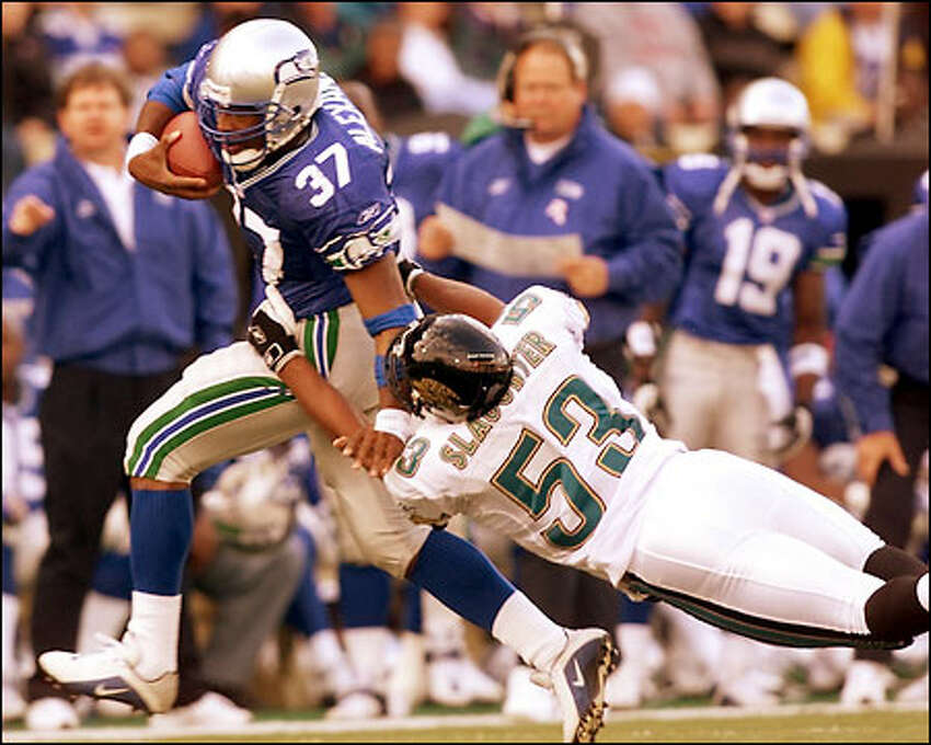 Shaun Alexander pushes away T.J. Slaughter during the third quarter of play at Husky Stadium.