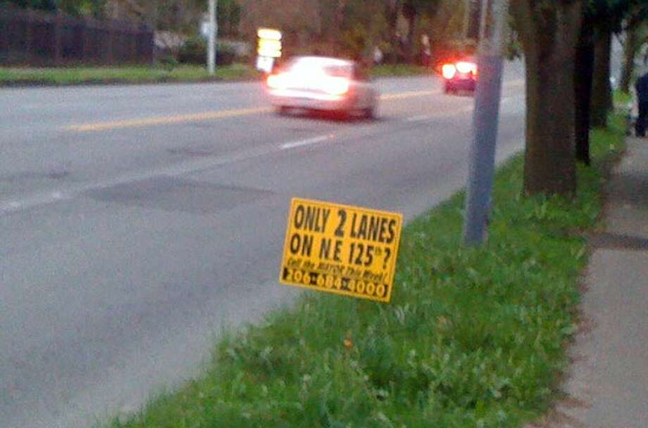 One of the anti-road diet signs on the Northeast 125th Street hill. City officials have recommended removing two car traffic lanes.