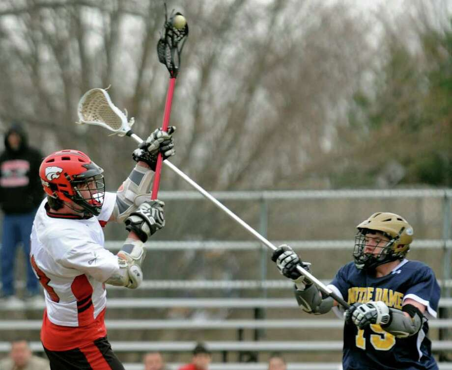 Masuk's #33 Connor Holloran, left, sends the ball in for one of the team's seventeen goals, as Notre Dame of Fairfield's #19 Jordan Garrison tries to block, during boys lacrosse action in Fairfield, Conn. on Wednesday April 6, 2011. Photo: Christian Abraham / Connecticut Post