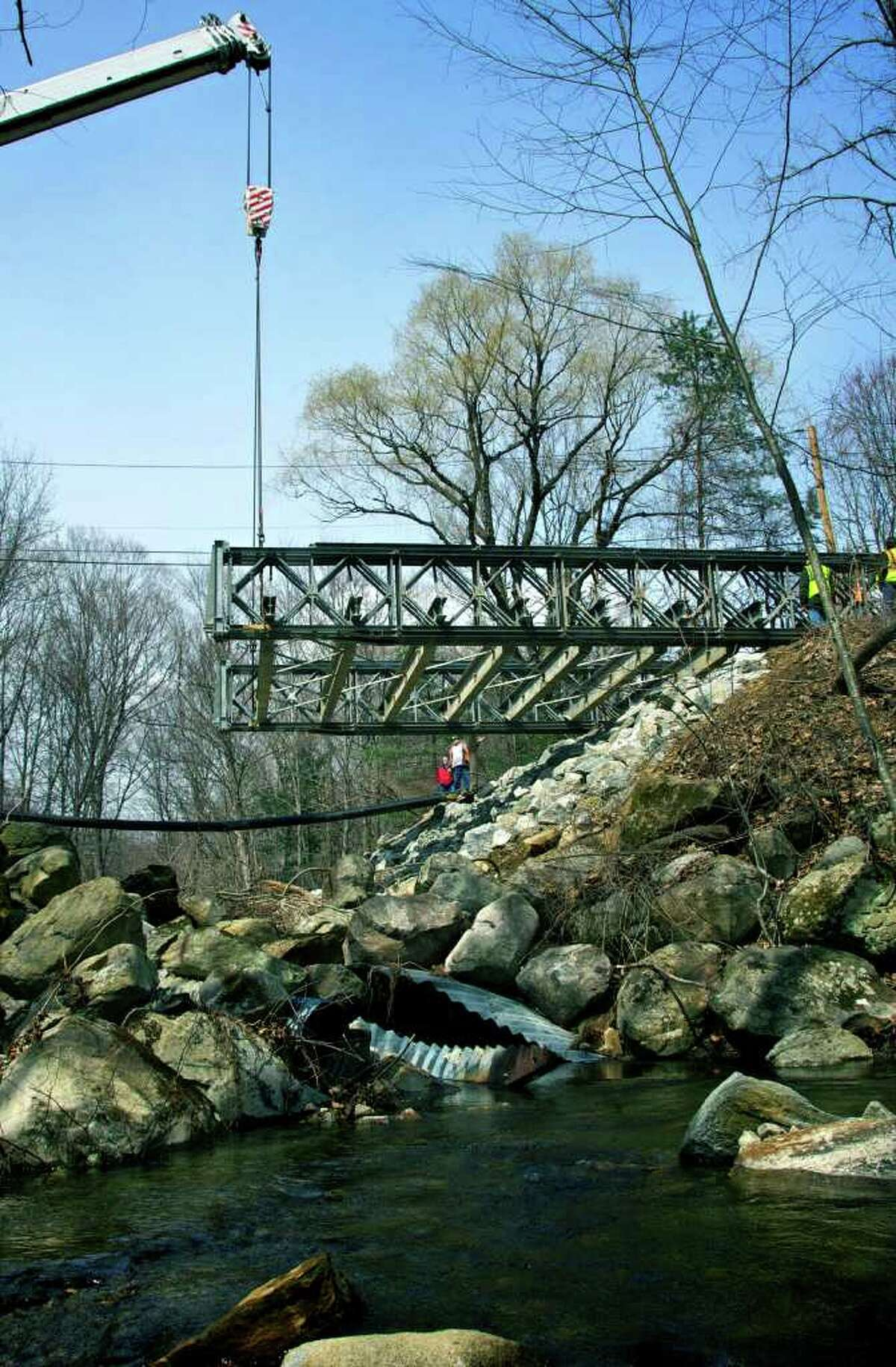 This turtle's eye view of Wednesday proceedings shows a temporary, 100-foot metal bridge being placed over the chasm on Chinmoy Lane in New Milford caused March 7 by rushing waters of the Merryall Brook. The brook's tranquil flow here belies the torrent that ripped away a large section of the Merryall district street.