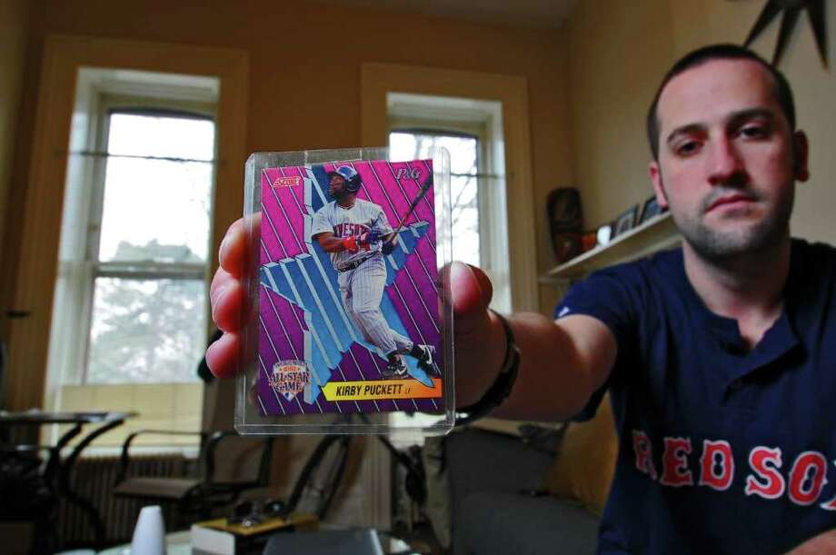 Andrew Woodman holds a 1992 Kirby Puckett baseball card that thieves missed when they robbed his apartment last year, including his boyhood baseball card collection with his prized Ken Griffey, Jr. rookie card,  on Wednesday April 6, 2011 in Albany, NY.  Puckett is Woodman's favorite player, from childhood. The robbers, who were caught in part because they still had the Griffey card on them, were recently sentenced to prison. The Griffey card is still with the Albany Police Department, Woodman not yet having had the time to retrieve it. (Philip Kamrass/ Times Union ) Photo: Philip Kamrass