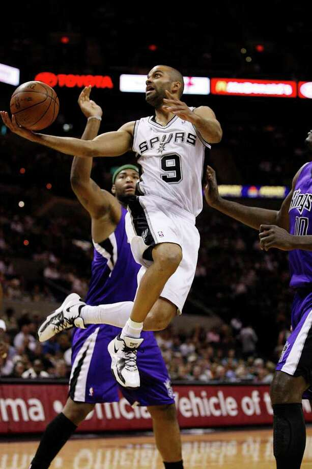 SPURS -- San Antonio Spurs Tony Parker flies by Sacramento Kings DeMarcus Cousins, left, and Samuel Dalembert during the first half at the AT&T Center, Wednesday, April 6, 2011. JERRY LARA/glara@express-news.net Photo: JERRY LARA, San Antonio Express-News / SAN ANTONIO EXPRESS-NEWS (NFS)
