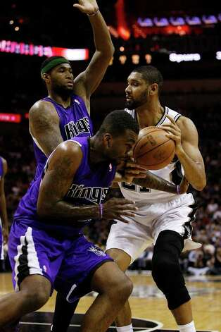 SPURS -- San Antonio Spurs Tim Duncan gets fouled by Sacramento Kings Donte Greene, foreground as teammate DeMarcus Cousins comes to help during the first half at the AT&T Center, Wednesday, April 6, 2011. JERRY LARA/glara@express-news.net Photo: JERRY LARA, San Antonio Express-News / SAN ANTONIO EXPRESS-NEWS (NFS)