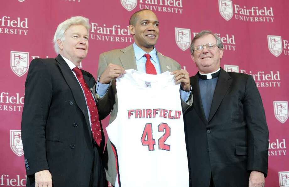 New Fairfield University men's basketball coach Sydney Johnson, flanked by Director of Athletics Eugene Doris, left, and Fairfield Univeristy President The Rev. Jeffrey P. von Arx, is introduced Wednesday April 6, 2011 at the John Barone Campus Center. Photo: Autumn Driscoll / Connecticut Post