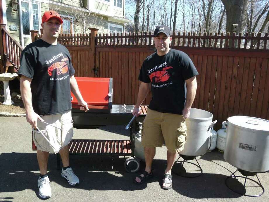 Jeff Seganos, left, and Mark Cehovsky, founding partners of Sea House Clambakes, stand in front of their catering equipment in the driveway of Cehovsky's Fairfield home. Photo: Contributed Photo