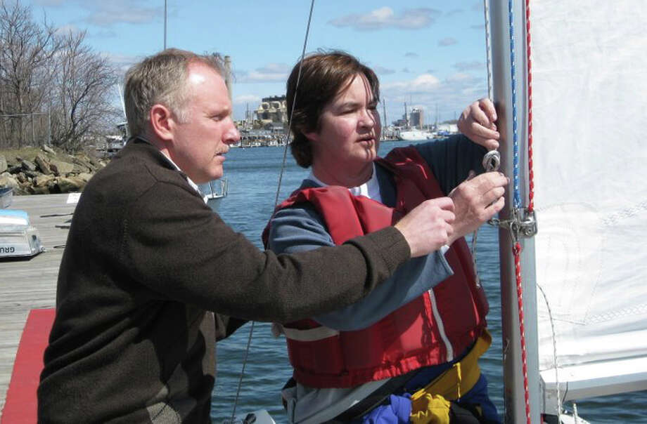 In preparation for the start of the sailing season, Christian Von Ancken, left, and  Ginny Perry Worcester of Community Sailing of Fairfield secure the spinnaker halyard to the mast on an Ideal 18. The sailing organization is offering a free series of seminars on safety, sailing techniques and seamanship. Photo: Contributed Photo / Fairfield Citizen contributed