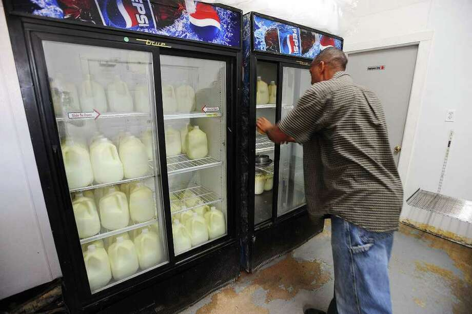 Kelvin Edwards refrigerates dairy products made from raw milk at the Pure Milk Farms in Winnie. Edwards sells the dairy products to visiting customers, but hopes for the state's approval on a proposed bill that would allow him to sell the goods at farmer's markets. Guiseppe Barranco/The Enterprise Photo: Guiseppe Barranco / Beaumont