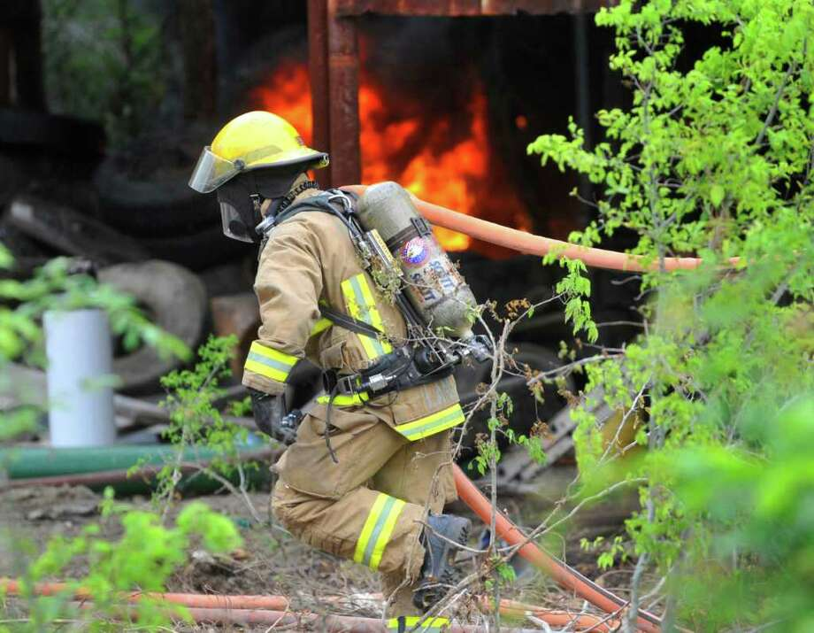 A BFD firefighter works to extinguish a tire fire in an abandoned building near Fourth Street and Rusk on Wednesday afternoon.  April 7, 2011.  Valentino Mauricio/The Enterprise Photo: Valentino Mauricio / Beaumont
