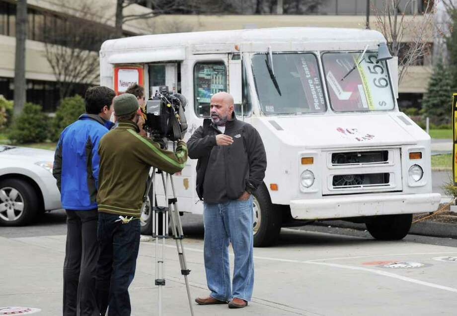 At right, Farahana Sami, representing the Sunoco gas station at 780 W. Putnam Ave., Byram, speaks with members of the media about a former ice cream truck parked on the property that sells cigarettes, Wednesday, April 6, 2011.  Sami said he is selling cigarettes out of the truck because it is on the Greenwich side of his property, since taxes are lower in Connecticut,therefor he can sell them cheaper and make a better profit.  The other half of the property is located on the New York State side of the border. Photo: Bob Luckey / Greenwich Time