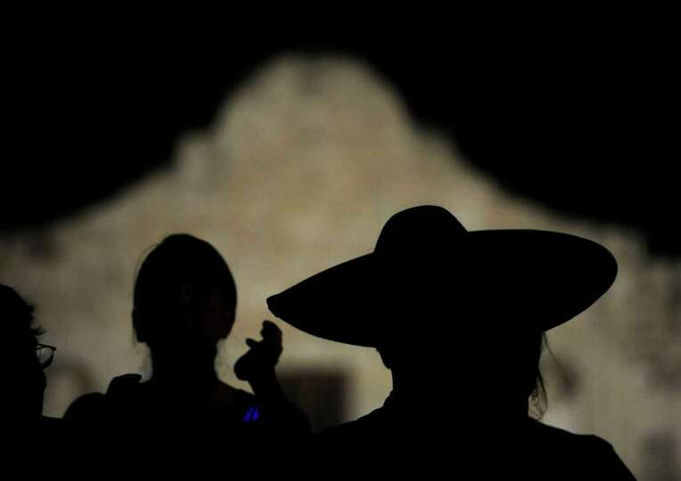 A charro stands in the shadows before the Alamo shrine during the Fiesta San Antonio 2011 opening
