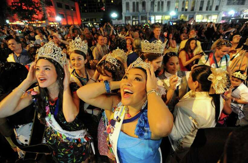 Miss Fiesta San Antonio 2011 Lauren Holt (left) and Krystal Diaz (front) react as fireworks and c