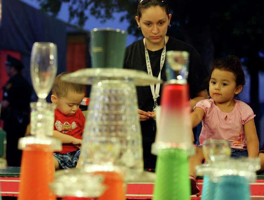 The Rodriguez family Sebastian, 1½, Marisela, and Promesa, 2½, play the Poor Man's Game during the Fiesta Carnival on April 7 at the Alamodome. Photo: EDWARD A. ORNELAS / SAN ANTONIO EXPRESS-NEWS (NFS)