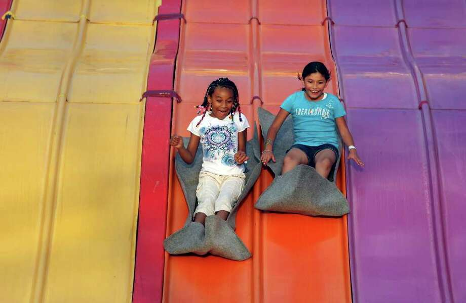Lillianna Bonneau, 8, (left) and Mia Torres, 8, enjoy the Drag Strip during the Fiesta Carnival on April 7 at the Alamodome. Photo: EDWARD A. ORNELAS / SAN ANTONIO EXPRESS-NEWS (NFS)