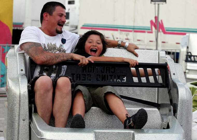 Randy Ochoa and his son Vincent, 9, enjoy the Sizzler during the Fiesta Carnival on April 7 at th
