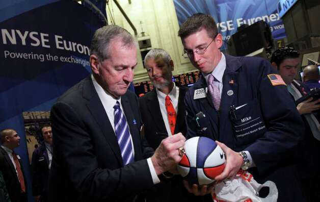 Jim Calhoun, left, head coach of the University of Connecticut's men's basketball team, autographs a basketball for trader Michael Jantz on the floor of the New York Stock Exchange before ringing the opening bell Friday, April 8, 2011. (AP Photo/Richard Drew) Photo: Richard Drew, AP / AP